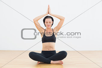 Woman in lotus pose with eyes closed at fitness studio