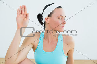 Fit woman with eyes closed at fitness studio