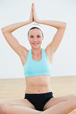 Smiling woman with joined hands over head at fitness studio