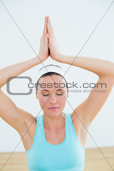 Toned relaxed woman with joined hands and eyes closed