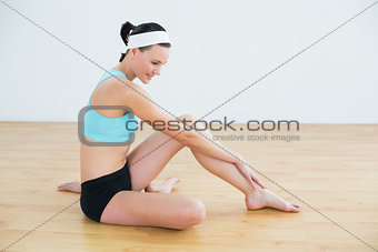 Thoughtful slim woman sitting in fitness studio