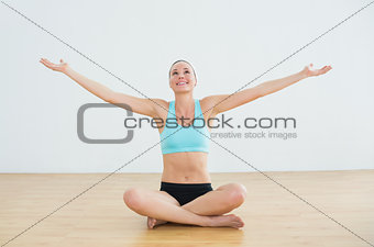 Toned woman sitting with arms outstretched in fitness studio