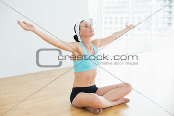 Smiling toned young woman sitting with arms outstretched