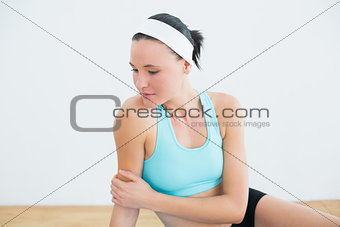 Thoughtful woman sitting in fitness studio