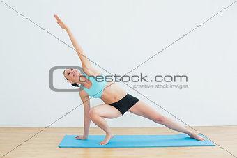 Slim woman doing the side plank yoga pose