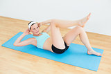 Sporty fit woman doing sit ups on exercise mat