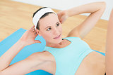 Fit woman doing sit ups on exercise mat