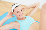 Smiling woman doing sit ups on exercise mat