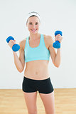 Fit woman holding dumbbells in fitness studio