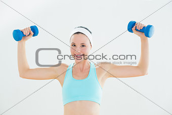 Fit smiling woman exercising with dumbbells