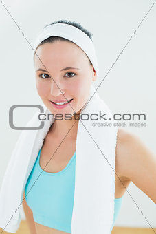 Slender woman with towel around neck in fitness studio