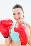 Close up of a beautiful young woman in red boxing gloves