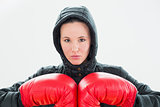 Beautiful young woman in hood and red boxing gloves