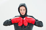 Beautiful woman in hood and red boxing gloves