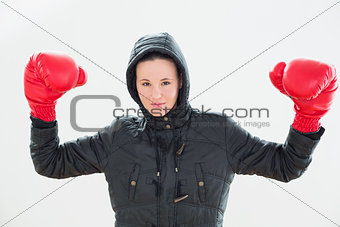 Smiling beautiful woman in hood and red boxing gloves