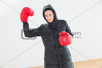 Tought woman in hooded jacket and red boxing gloves