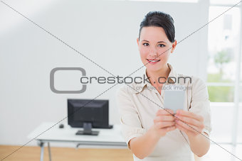 Businesswoman holding a cellphone in office