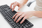 Midsection of a businesswoman typing on keyboard