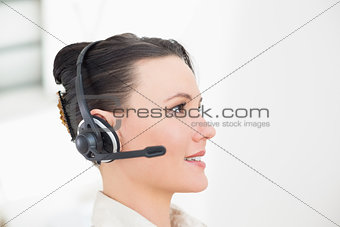 Close up side view of a beautiful businesswoman using headset