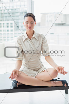 Elegant businesswoman in lotus position with eyes closed at office