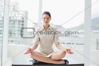 Smart businesswoman sitting in lotus position at office