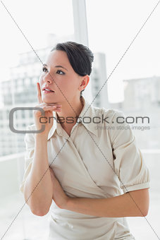 Thoughtful businesswoman standing in office