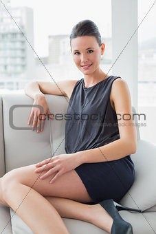 Beautiful well dressed young woman sitting on sofa