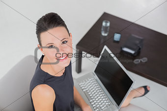 Beautiful well dressed young woman with laptop on sofa