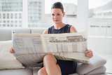 Beautiful businesswoman reading newspaper on sofa