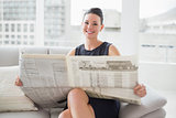 Smiling beautiful businesswoman reading newspaper on sofa