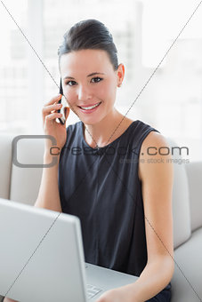 Beautiful smiling well dressed woman using laptop and cellphone