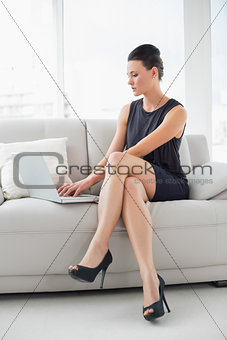 Beautiful well dressed woman using laptop on sofa