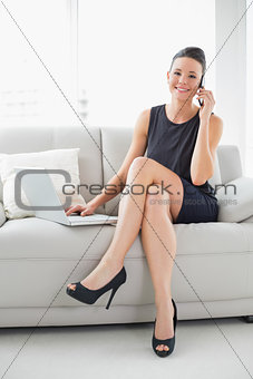 Beautiful well dressed woman using laptop and cellphone