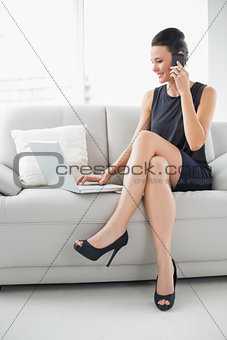 Beautiful well dressed woman using laptop and cellphone on sofa