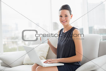 Beautiful well dressed woman using laptop while having coffee on sofa