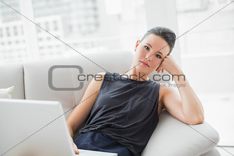 Tired beautiful well dressed woman with laptop sitting on sofa