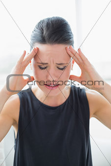 Close up of a young businesswoman suffering from headache