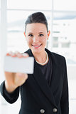 Elegant businesswoman holding up a business card in office