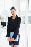Elegant businesswoman with folder in office
