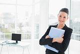 Elegant businesswoman leaning on glass wall with folder