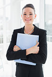 Elegant businesswoman standing against office glass wall with folder