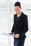 Businesswoman with folder standing against office glass wall