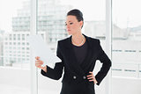 Serious elegant woman reading a document in office