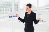 Businesswoman with graphs standing in bright office