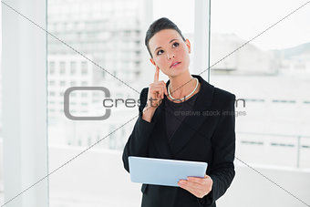 Thoughtful elegant businesswoman holding tablet PC