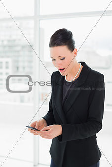 Shocked elegant businesswoman looking at mobile phone