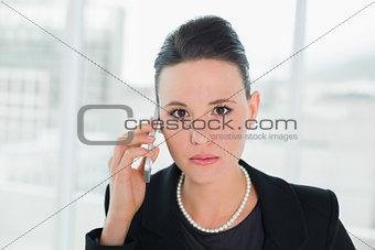 Close up of a serious elegant businesswoman using cellphone