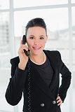 Smiling elegant businesswoman using landline phone
