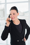 Businesswoman using landline phone as she looks away