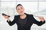 Frustrated elegant businesswoman with telephone cable around her neck